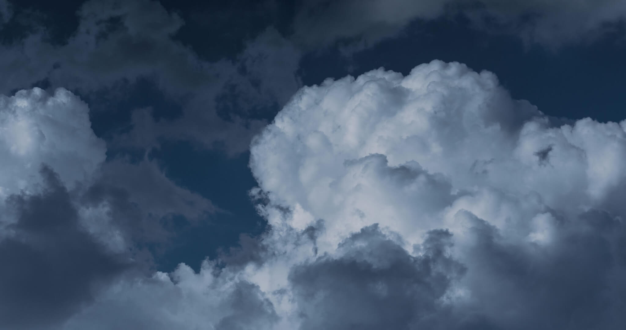 An image of clouds in a dark blue sky