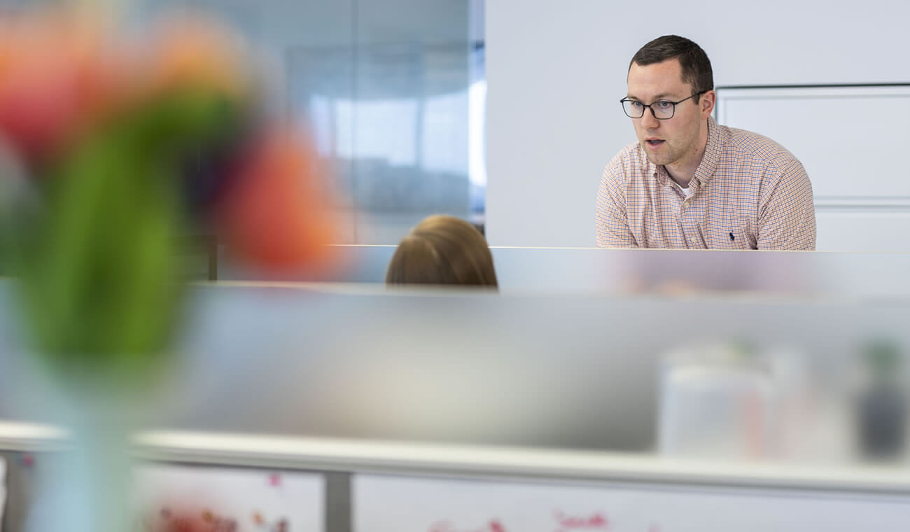 Man standing at a workstation talking to someone sitting down