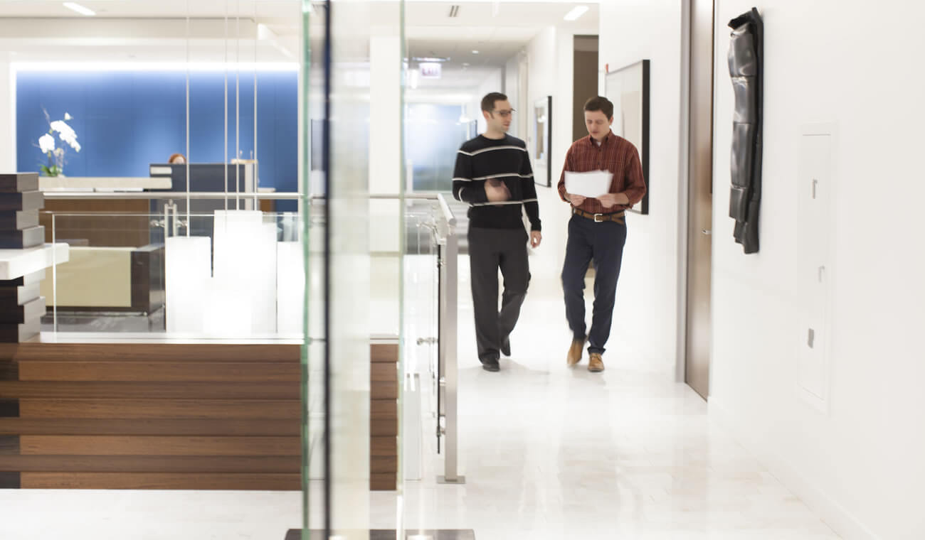 Two men in discussions walking down the hall