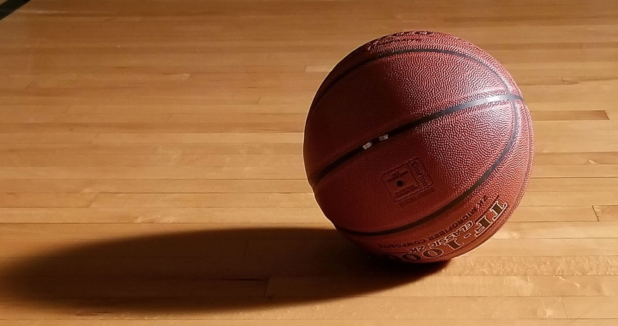 An image of a basketball on a wood floor