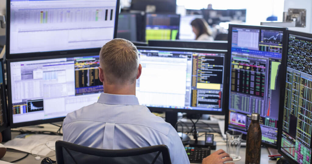 Trading desk with man working at his computer